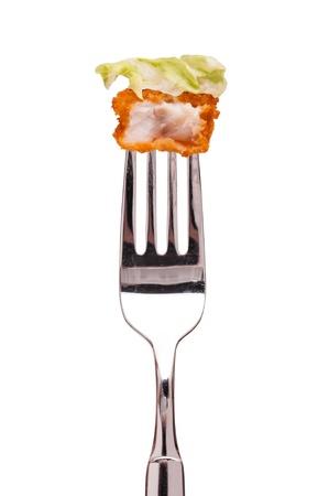 白い分離揚げ魚指とフォークの上のグリーン サラダ