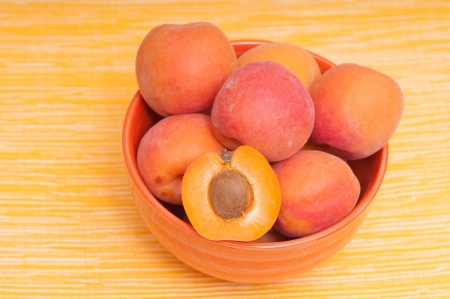 apricot kernels: Apricots in a bowl with yellow tablecloth