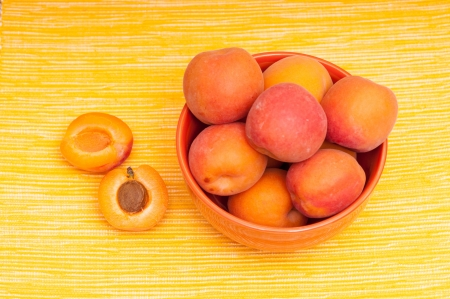 apricot kernel: Apricots with apricot kernel in bowl on a yellow tablecloth