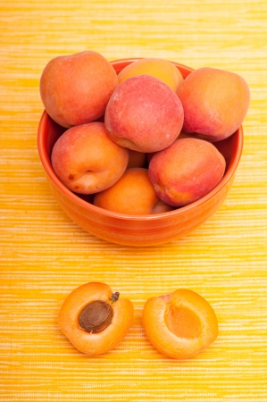 apricot kernel: Apricot with apricot kernel beneath a bowl in vertical format