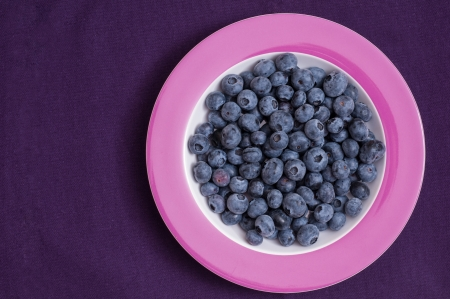 bilberries: Bilberries on a plate and tonal tablecloth