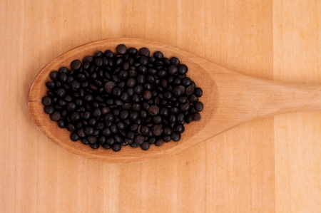 Close-up of beluga lentils on a wooden spoon photo