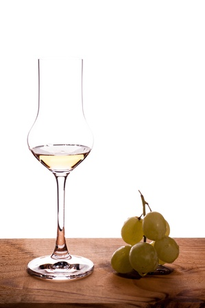 Italian grappa with grapes on a wooden board Standard-Bild