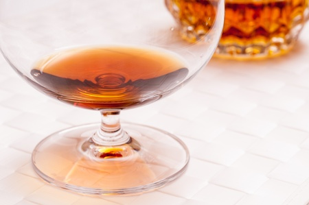 amber coloured: Brown brandy in a cognac glass on a white background Stock Photo