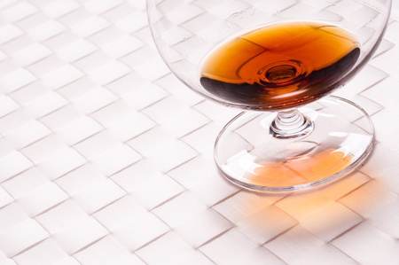 amber coloured: Old amber brandy in a glass on a white background