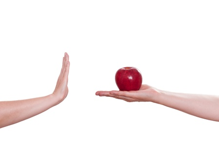 White isolated hand is refusing an red apple