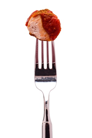 White isolated curry sausage with sauce on a fork