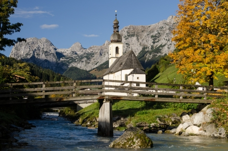 Church in Ramsau with mountain brook and wooden bridge photo