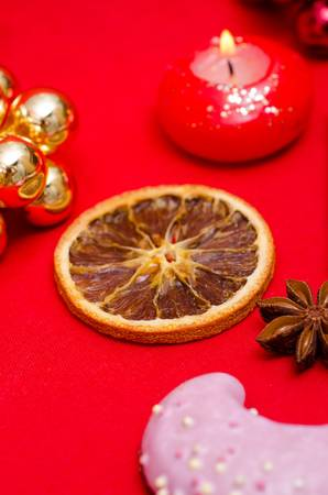 Dried slice of an orange and a burning red candle Stock Photo - 15835525