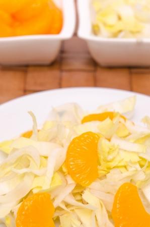 Mandarines orange avec de la salade de chicorée sur une plaque blanche