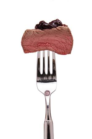 Meat filet of venison on a white isolated fork