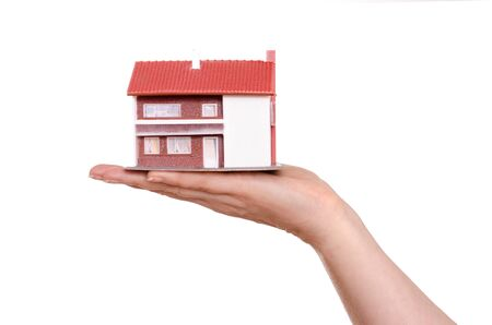 White isolated residence house on a female hand photo