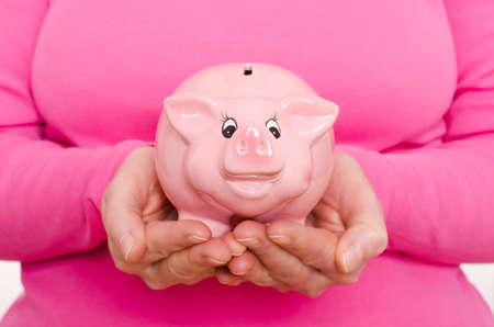 Two female hands are holding a pink piggy bank photo