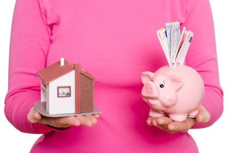 House and pink piggy bank in a female hands photo