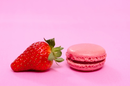 speciality: Sweet dessert of red french speciality macaron and a strawberry