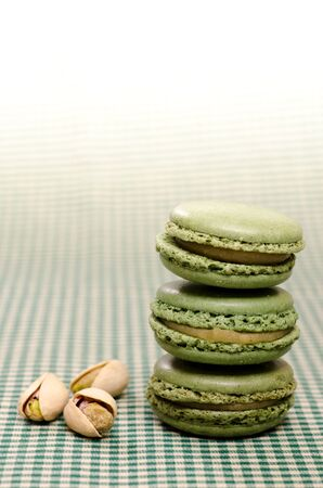 sugared: Three green Macarons with pistachios in vertical format