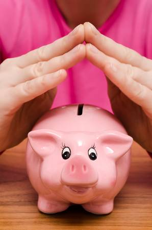 Two female hands over a pink piggy bank photo