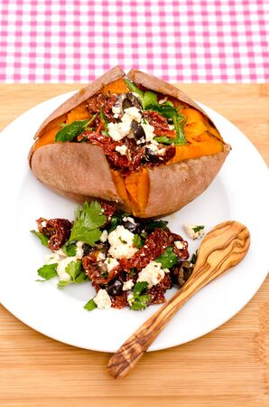 Fried sweet potato with feta cheese, olives, parsley and dried tomatoes photo