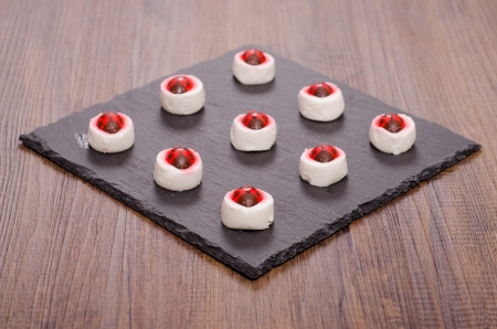 9 little soft goat cheeses with sugar ladybirds on it Stock Photo - 18852147