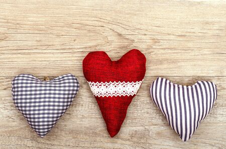 Three hearts of cloth on old wooden board photo