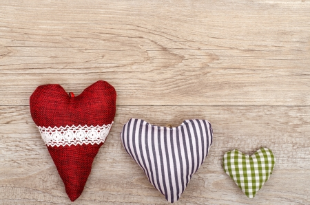 Weathered wooden board with three hearts of cloth photo