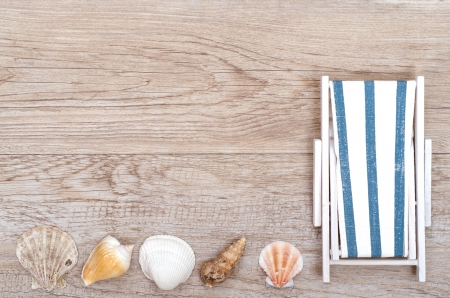 Deckchair and sea shells on old weathered wooden board photo