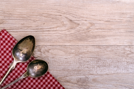 Two old silver spoons on checkered cloth and weahtered wood photo