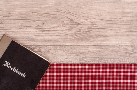 Cookbook on checkered table cloth and old wood photo