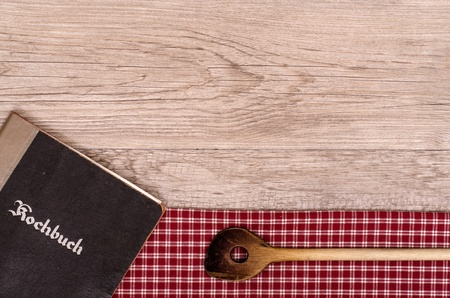 Recipe book and wooden spoon on a checkered table cloth photo