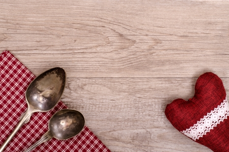 Silver spoon and table cloth with heart on a wooden board photo