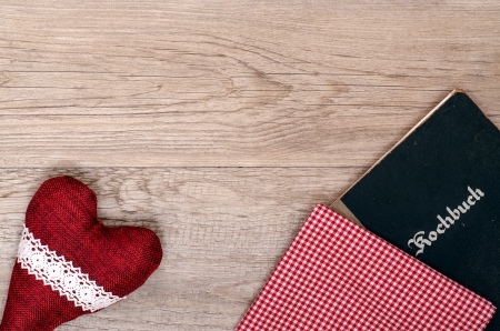 Red heart with checkered cloth and book on old wood photo