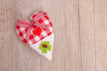 Heart of cloth with green shamrock and red lady bird Stock Photo - 19318288