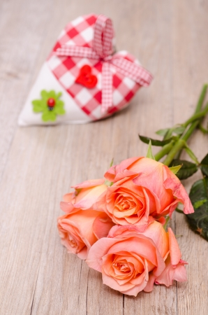Declaration of love with orange roses and heart of cloth Stock Photo - 19318277