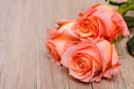 Three orange flowers of roses on wooden board photo
