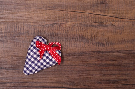 Blue checkered heart with red ribbon on a wooden board photo