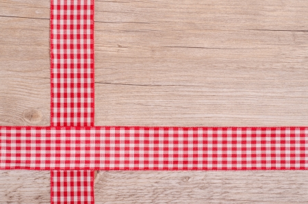 Red and white checkered ribbons on old wood photo