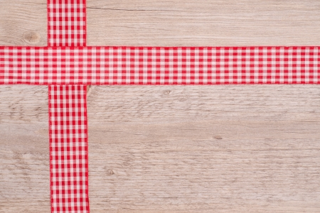 Ribbons of cloth red and white checkered on a wooden board photo