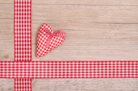 Red checkered heart and ribbon on wood as background photo