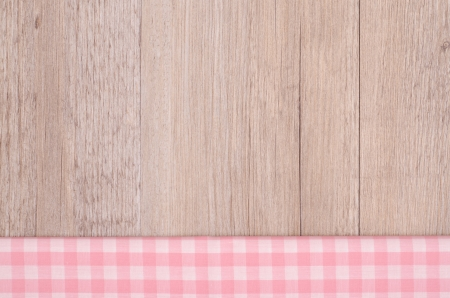 Pink and white checkered cloth on wood as background photo