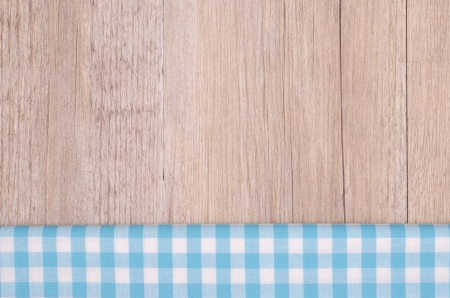 Light blue checkered cloth on wood as background photo
