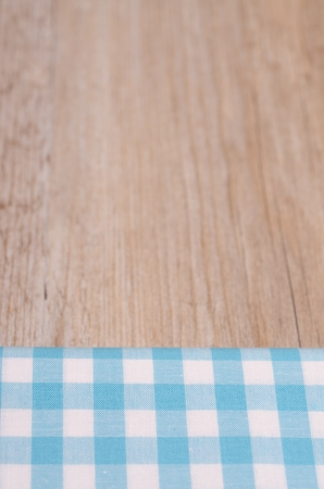 Light blue checkered cloth with blurred wood as background photo