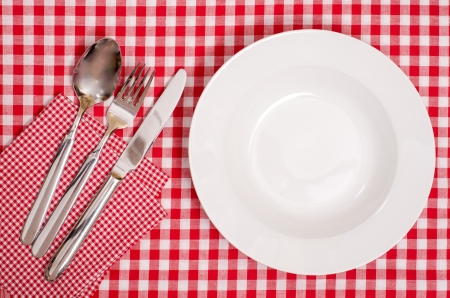 White plate with cutlery of spoon, fork and knife photo