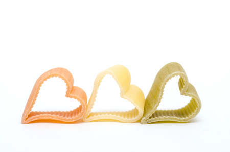 Heart shaped italian pasta in orange, yellow and green photo