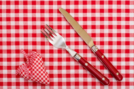 Knife and fort with red checkered heart and bow on table cloth photo