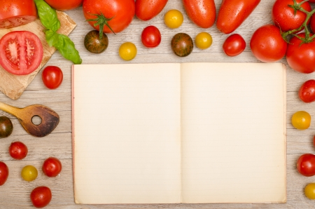 Frame of wet tomatoes with wooden spoen and text space in a recipe book