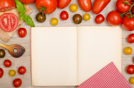 Different tomatoes, basil, wooden spoon, napkin and a recipe book with text space photo