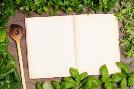 Green herbs as frame around a cookbook for recipes Zdjęcie Seryjne