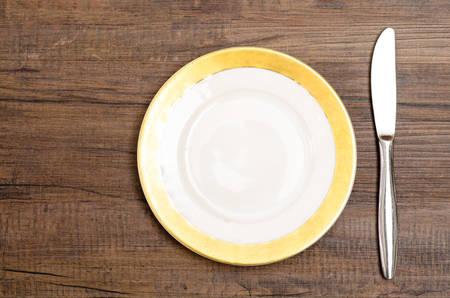 dessert plate: Piatto da dessert in porcellana con un coltello su un tavolo di legno Archivio Fotografico