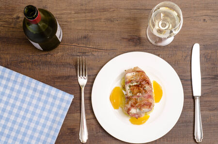 cod fish: Roastad fish with bacon and white wine on a brown wooden table
