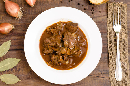 Plate with venison goulash from deer with onions